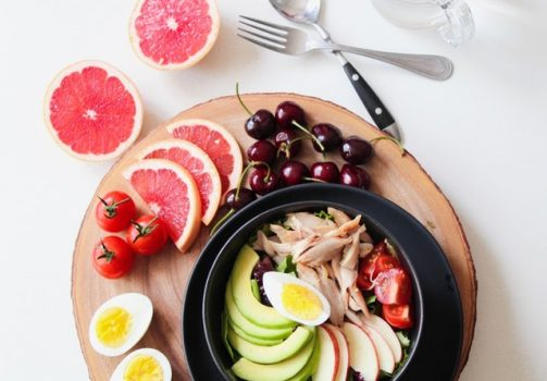 Plastic container with delicious food on wooden table. Fruits surround the table.