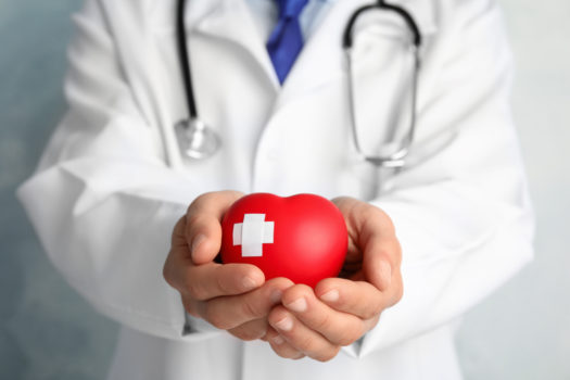 Doctor holding red heart with adhesive plasters, closeup view.
