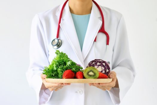 Doctor holding fresh fruit and vegetable, Healthy diet, Nutrition food as a prescription for good health.