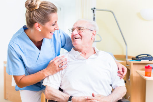 Senior man and old age nurse in nursing home.