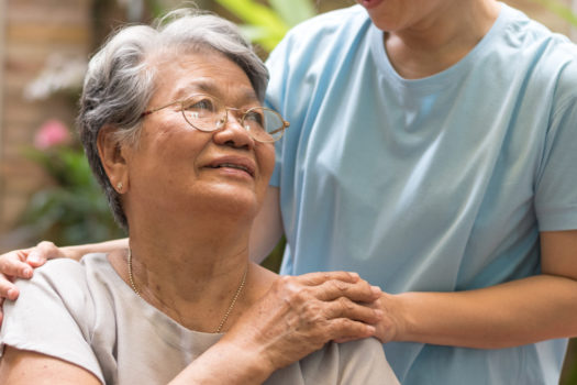 Care giver hand on happy elderly senior patient to comfort in hospital or hospice nursing home or hospice