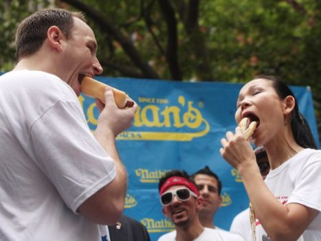 A man and a woman are eating hotdogs, as they compete at the Nathan's Hot Dog contest.