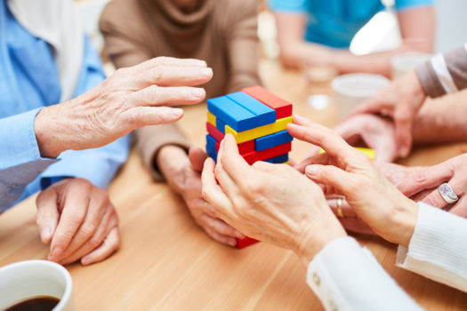Group of seniors with dementia builds a tower in the nursing center from colorful building blocks