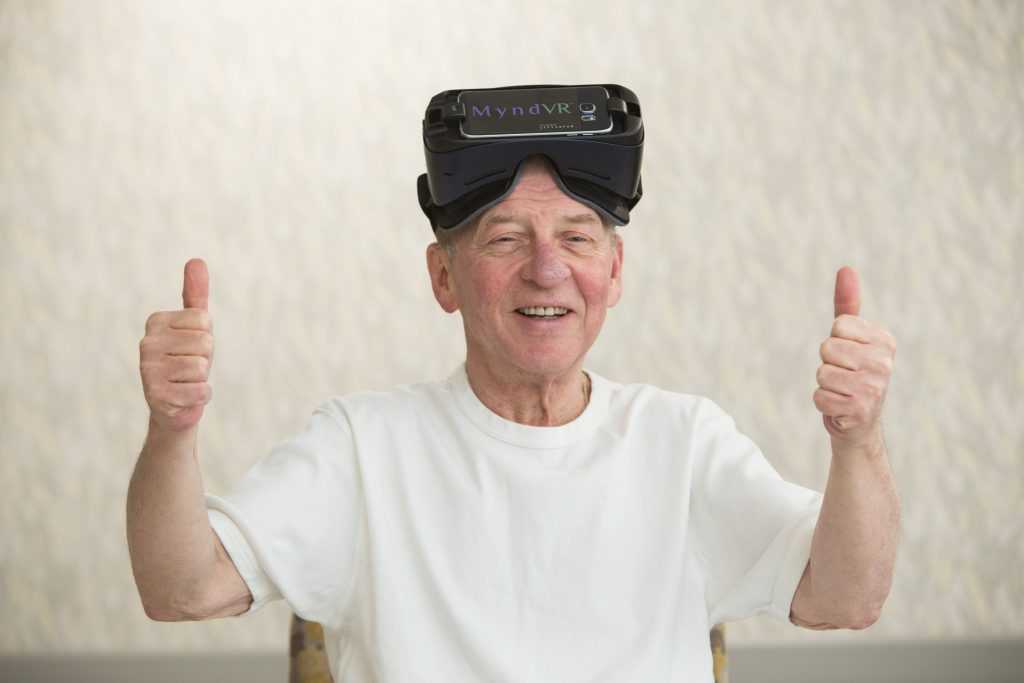 A senior is wearing virtual reality goggles and giving two thumbs up.