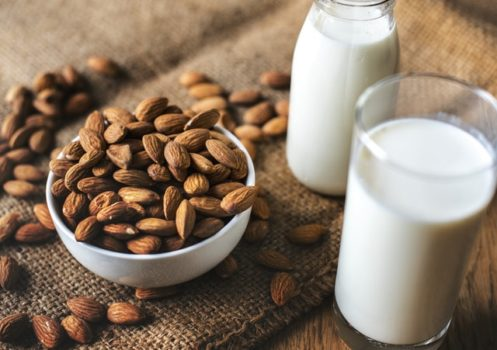 Overflowing bowl of almonds on a wooden table next to two glasses of almond milk.