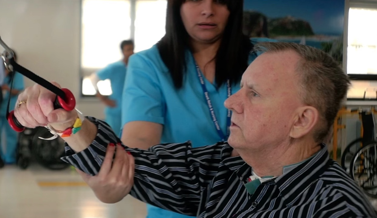 Medical professional is helping a senior man with rehabilitation.